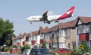 A Qantas Boeing 747-400 approaching runway 27L at London Heathrow Airport, England. The houses are in Myrtle Avenue, at the south east corner of the airport. Photographer's note: I know this aircraft looks as though it was inserted in a graphics program but the picture is genuine. Aircraft pass close to Myrtle Avenue every 2 minutes when 27L is in use, so getting shots like this is easy. Photographed by Adrian Pingstone.