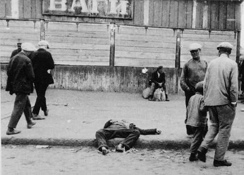 Passers-by and the corpse of a starved man on a street in Kharkiv during the famine in Ukraine, 1932.
